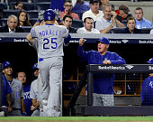 Manager Ned Yost of the Kansas City Royals congratulates Kendrys Morales after he hit a solo home run in the seventh inning against the New York...