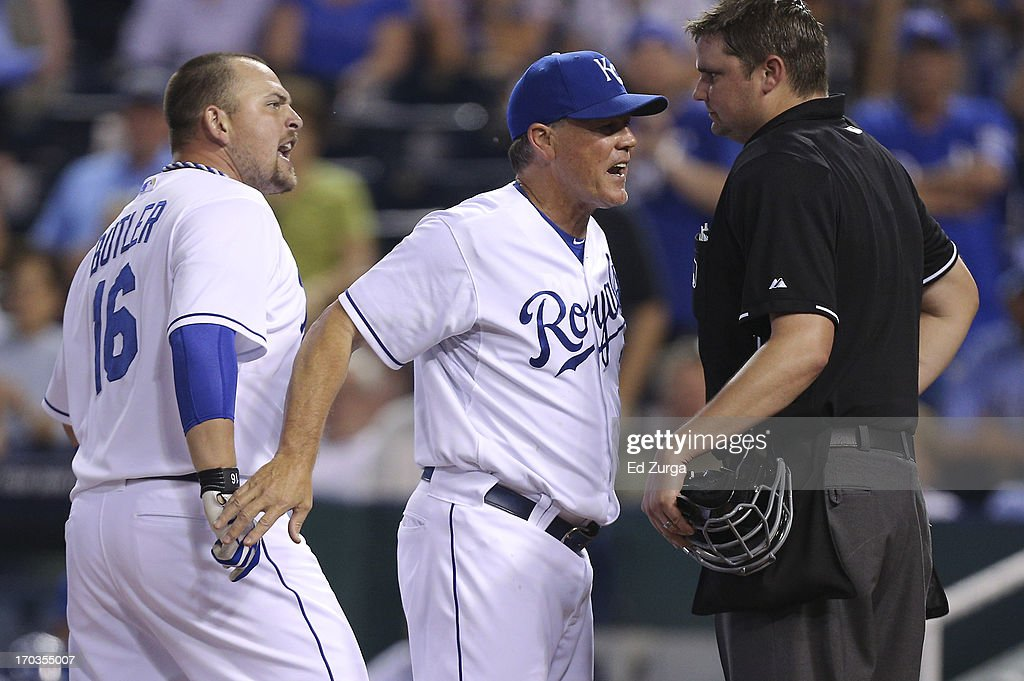 Manager Ned Yost #3 of the Kansas City Royals gets between Billy Butler #16 and plate umpire Jordan Baker after Butler was ejected for arguing strike calls in the ninth inning during a game against the Detroit Tigers at Kauffman Stadium on June 11, 2013 in Kansas City, Missouri.