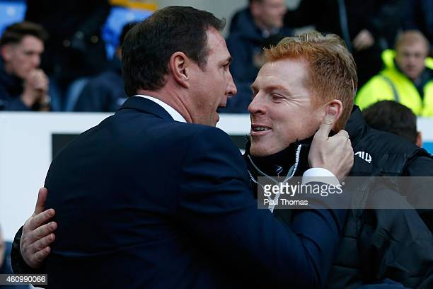 Manager Neil Lennon of Bolton hugs Manager Malky Mackay of Wigan during the FA Cup Third Round match between Bolton Wanderers and Wigan Athletic at...