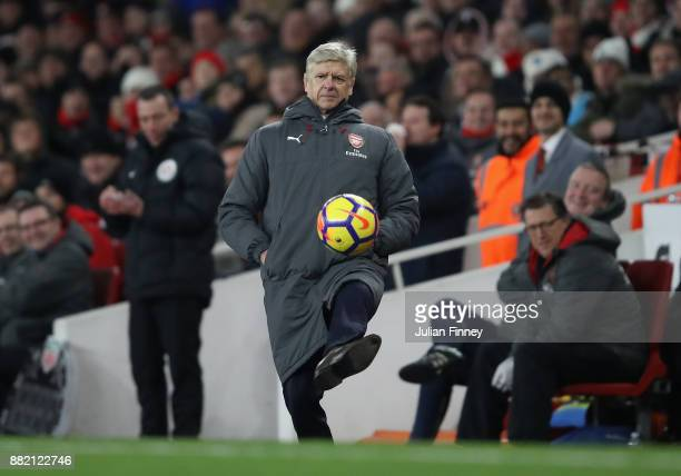 Manager of Arsenal Arsene Wenger kicks the ball back during the Premier League match between Arsenal and Huddersfield Town at Emirates Stadium on...