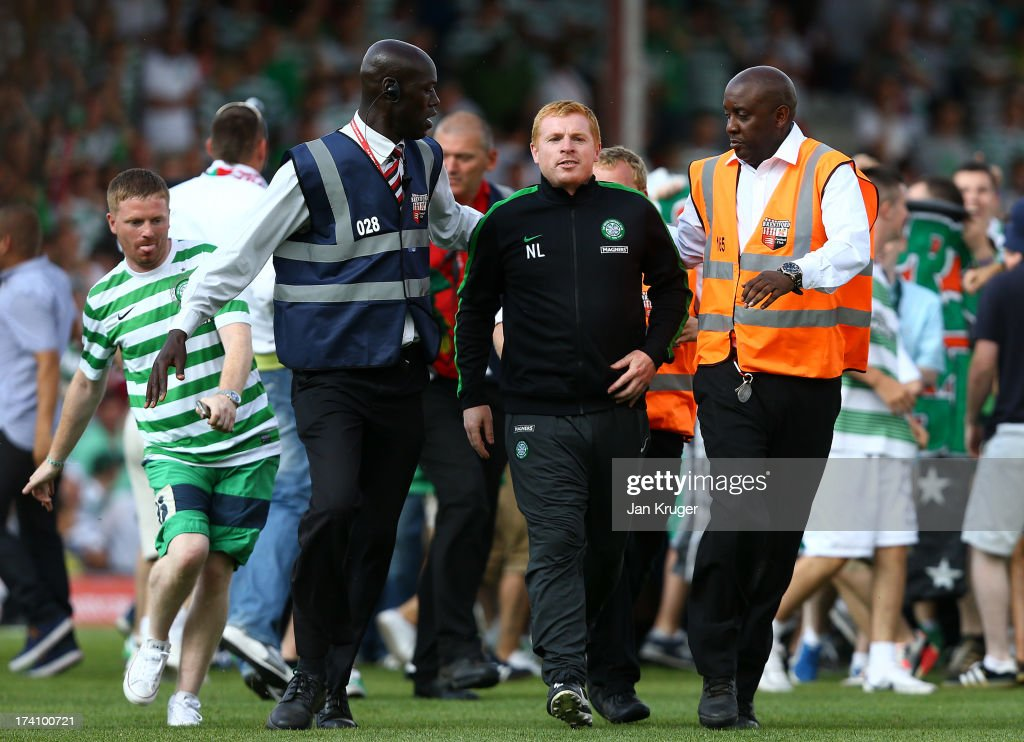 Manager of Celtic Neil Lennon is escorted off the pitch as traveling fans invade the pitch during a pre season friendly match between Brentford and Celtic at Griffin Park on July 20, 2013 in Brentford, England.