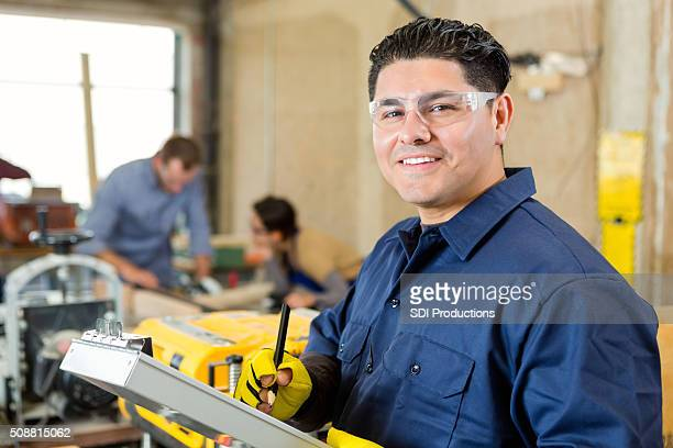 Manager of machine shop smiling while checking customer orders