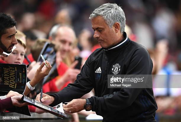 Manager of Manchester United Jose Mourinho signs autographs during the Wayne Rooney Testimonial match between Manchester United and Everton at Old...