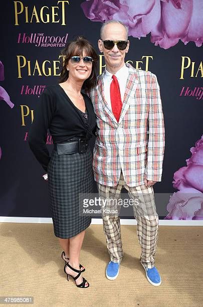Manager of Piaget Natacha Hertz and John Waters pose in the Piaget Lounge during the 2014 Film Independent Spirit Awards at Santa Monica Beach on...