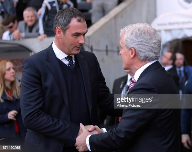 Manager of Swansea City Paul Clement greets manager of Stoke City Mark Hughes in the dug out during the Premier League match between Swansea City and...