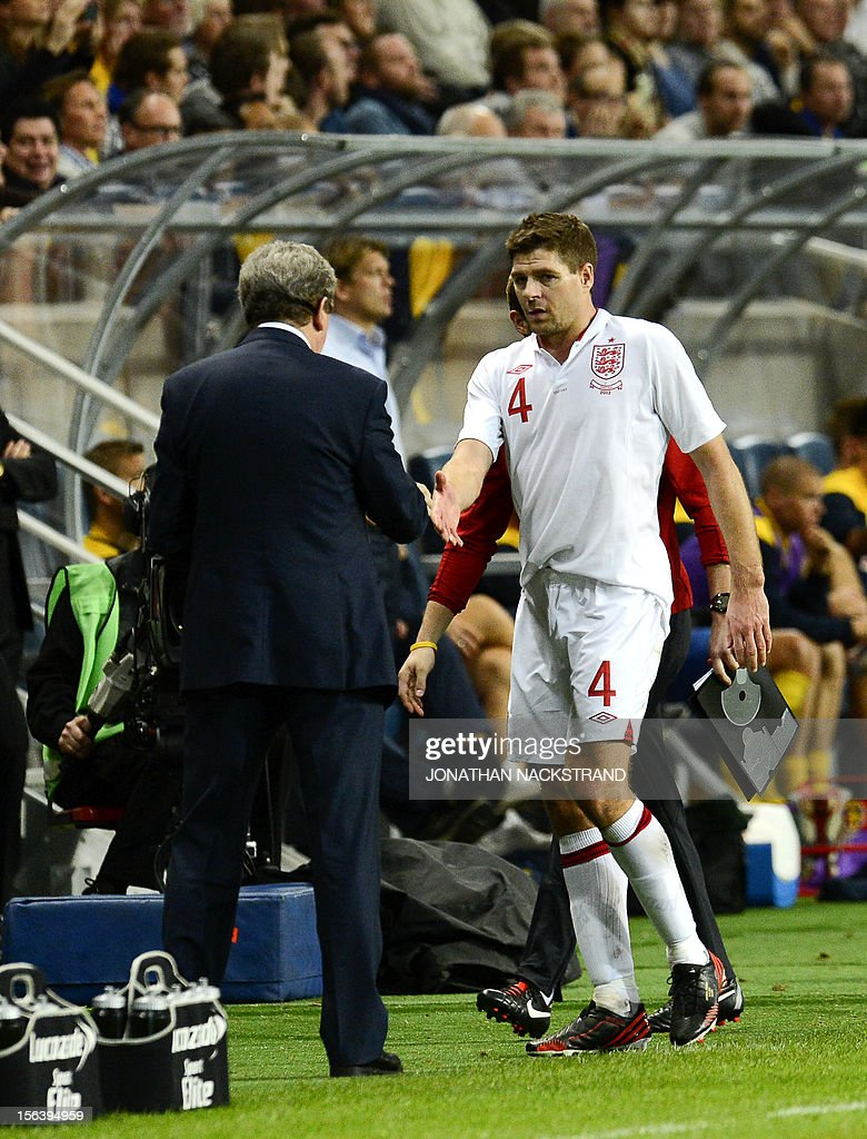 Manager of the England football team Roy Hodgson shakes hands with midfielder and team captain Steven Gerrard as he leaves the pitch during the FIFA World Cup 2014 friendly match Sweden vs England at the 'Friends Arena' in Stockholm on November 14, 2012. Sweden beat England 4-2.AFP PHOTO/JONATHAN NACKSTRAND