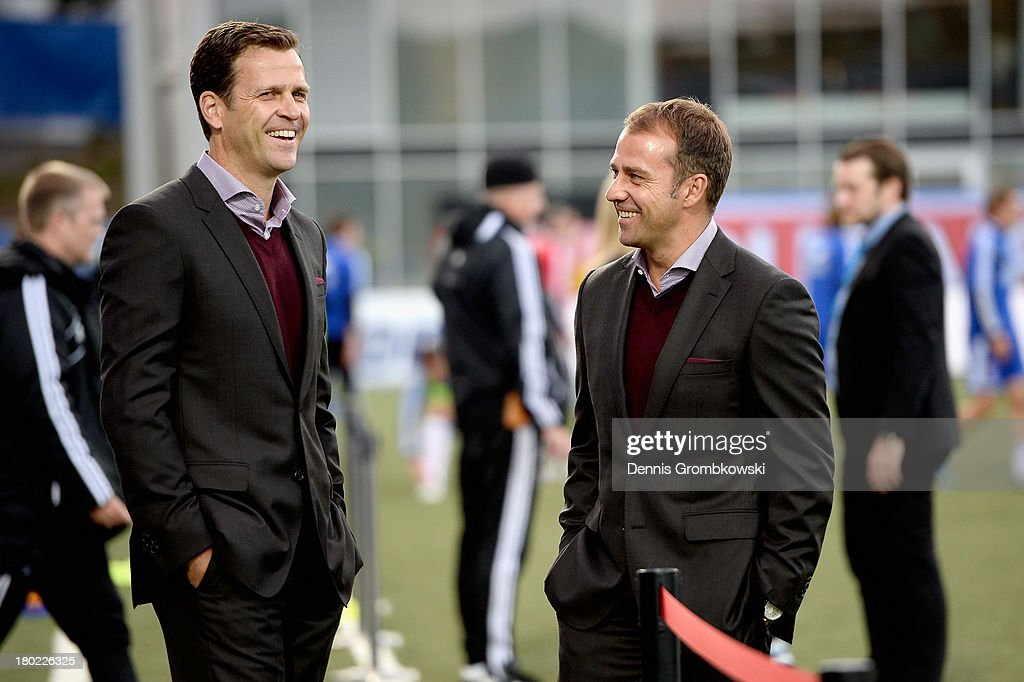 Manager Oliver Bierhoff and assistant coach Hans-Dieter Flick of Germany joke prior to the FIFA 2014 World Cup Qualifier match between Faeroe Islands and Germany on September 10, 2013 in Torshavn, Denmark.