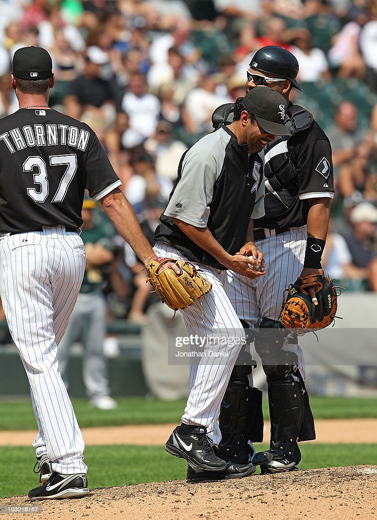 Manager <a gi-track='captionPersonalityLinkClicked' href=/galleries/search?phrase=Ozzie+Guillen&family=editorial&specificpeople=210514 ng-click='$event.stopPropagation()'>Ozzie Guillen</a> #13 of the Chicago White Sox laughs after being swiped by pitcher Matt Thorton #37 after taking Thorton out of a game as <a gi-track='captionPersonalityLinkClicked' href=/galleries/search?phrase=Ramon+Castro&family=editorial&specificpeople=208997 ng-click='$event.stopPropagation()'>Ramon Castro</a> #27 watches in the 8th inning against the Oakland Athletics at U.S. Cellular Field on August 1, 2010 in Chicago, Illinois. The White Sox defeated the Athletics 4-1.