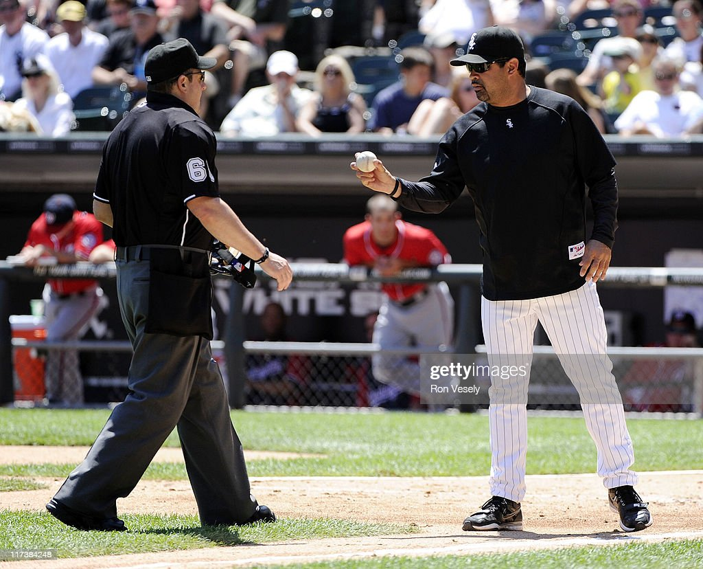 Manager Ozzie Guillen #13 of the Chicago White Sox points to the baseball while discussing a hit by pitch call on Roger Bernadina #2 of the Washington Nationals by home plate umpire Marty Foster #60 during the fourth inning on June 26, 2011 at U.S. Cellular Field in Chicago, Illinois. The Nationals defeated the White Sox 2-1.