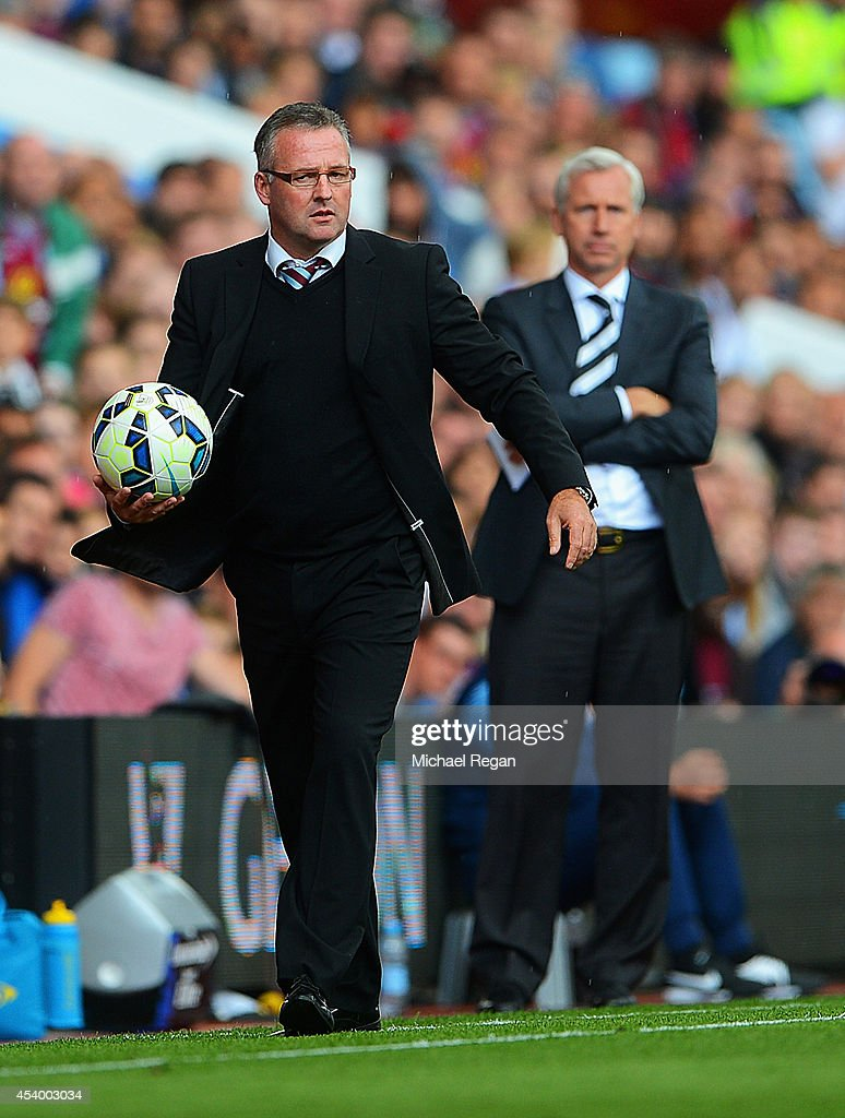 Manager Paul Lambert (L) of Aston Villa gathers the ball with Alan Pardew, manager of Newcastle United looking on during the Barclays Premier League match between Aston Villa and Newcastle United at Villa Park on August 23, 2014 in Birmingham, England.