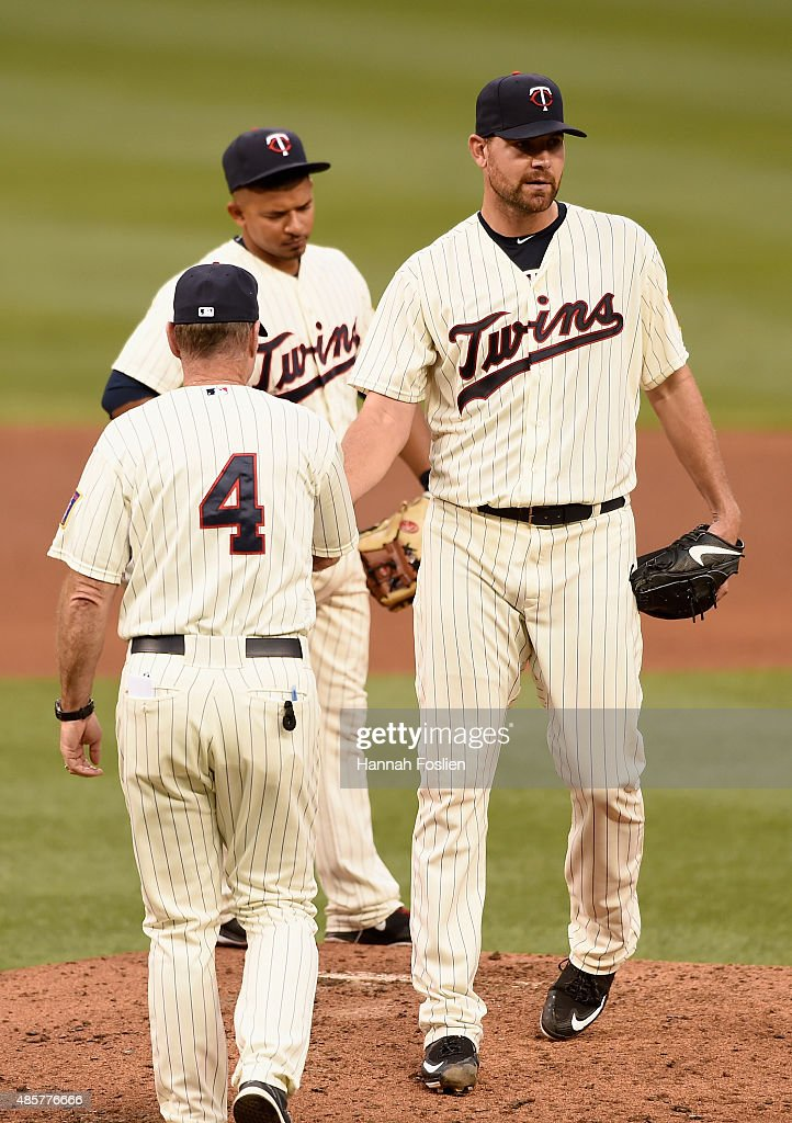 Manager Paul Molitor #4 of the Minnesota Twins pulls Mike Pelfrey #37 from the game against the Houston Astros as teammate Eduardo Escobar #5 looks on during the fourth inning on August 29, 2015 at Target Field in Minneapolis, Minnesota. The Astros defeated the Twins 4-1.