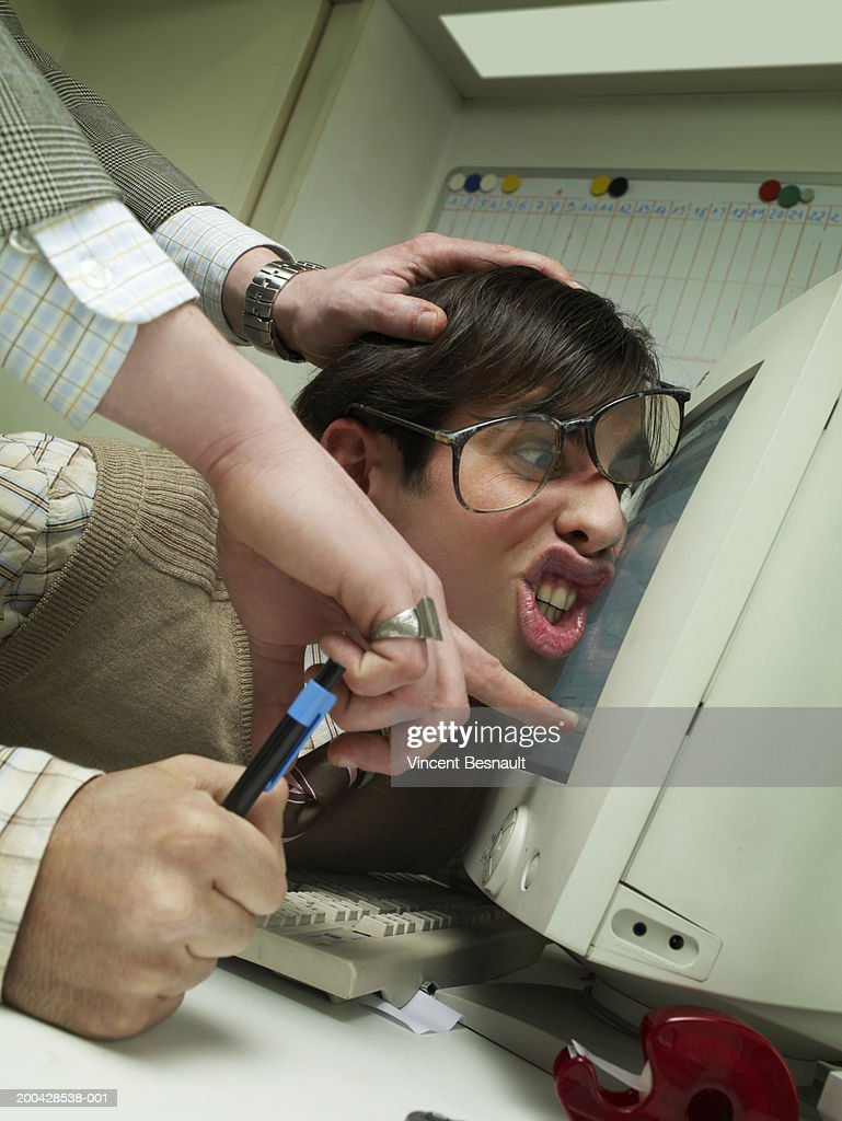 Manager pushing office worker's face against computer screen : Stock Photo