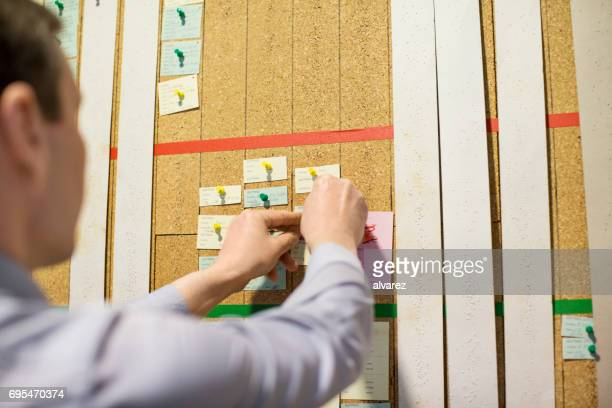 Manager putting a paper note on cork board