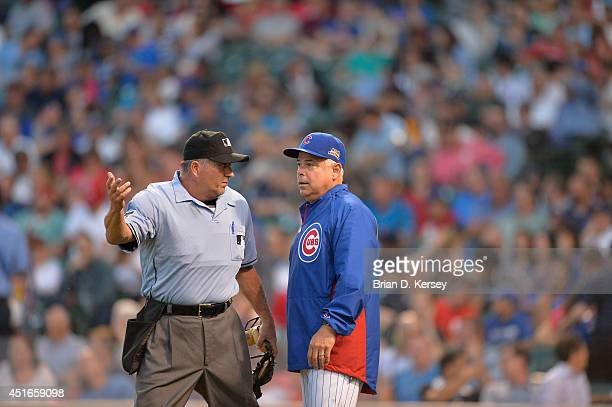 Manager Rick Renteria of the Chicago Cubs talks with home plate umpire Dale Scott during the third inning against the Cincinnati Reds at Wrigley...