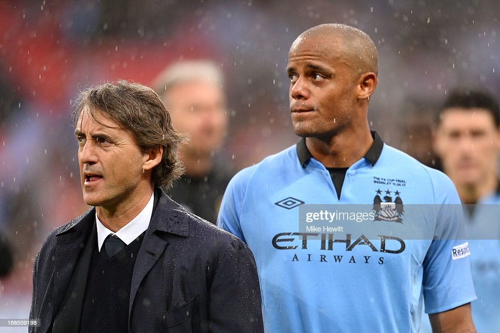 Manager Roberto Mancini of Manchester City and Vincent Kompany look dejected in defeat after the FA Cup with Budweiser Final between Manchester City and Wigan Athletic at Wembley Stadium on May 11, 2013 in London, England.