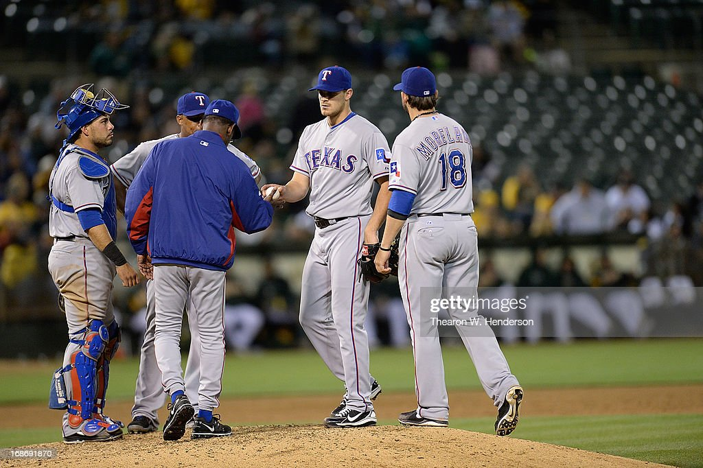 Manager <a gi-track='captionPersonalityLinkClicked' href=/galleries/search?phrase=Ron+Washington&family=editorial&specificpeople=225012 ng-click='$event.stopPropagation()'>Ron Washington</a> #38 of the Texas Rangers takes the ball from pitcher <a gi-track='captionPersonalityLinkClicked' href=/galleries/search?phrase=Justin+Grimm&family=editorial&specificpeople=9480126 ng-click='$event.stopPropagation()'>Justin Grimm</a> #51 taking him out of the game against the Oakland Athletics in the six inning at O.co Coliseum on May 13, 2013 in Oakland, California.