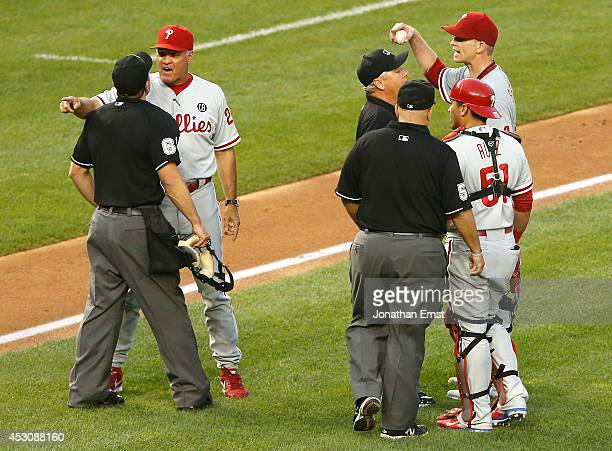 Manager Ryne Sandberg of the Philadelphia Phillies and his starting pitcher AJ Burnett argue with umpires after their ejections following Burnett's...