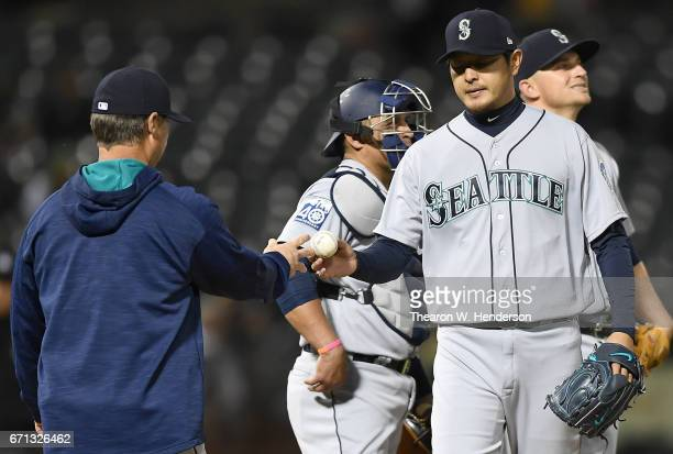Manager Scott Servais of the Seattle Mariners takes the ball from starting pitcher Hisashi Iwakuma taking him out of the game against the Oakland...