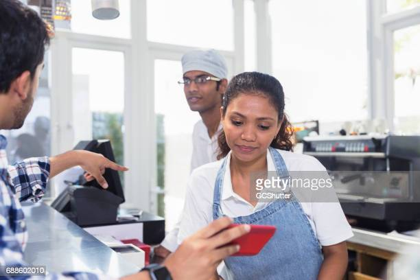 Manager showing his baristas the menu for the day
