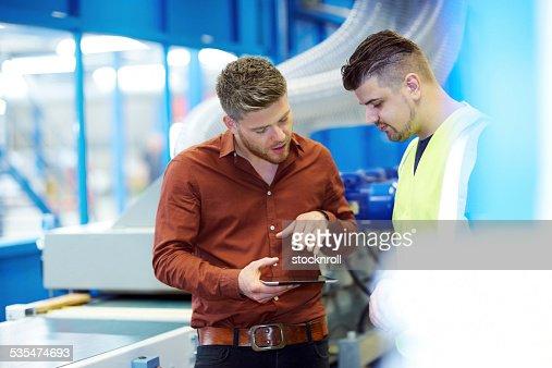 マネージャーに新しいデザインを示すデジタルタブレットをフォアマン