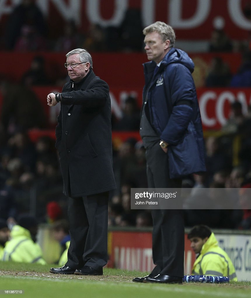 Manager Sir Alex Ferguson of Manchester United checks his watch as David Moyes of Everton watches from the touchline during the Barclays Premier League match between Manchester United and Everton at Old Trafford on February 10, 2013 in Manchester, England.