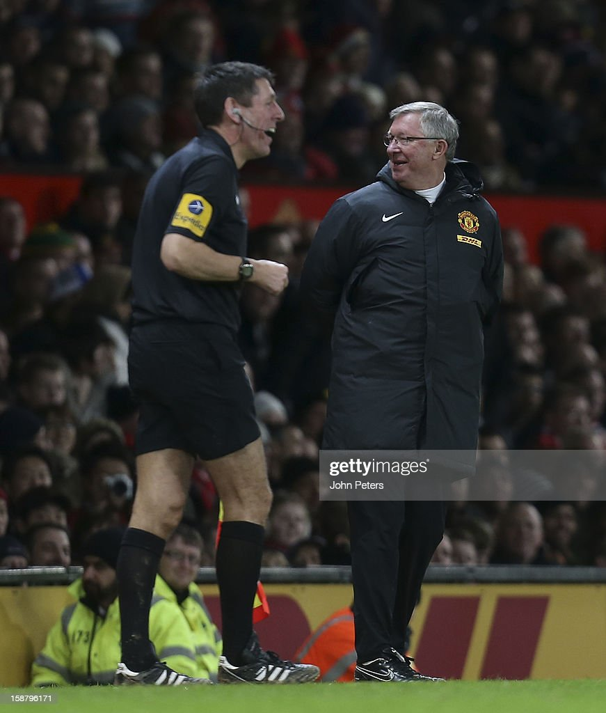 Manager Sir Alex Ferguson of Manchester United shares a joke with assistant referee Andy Garratt during the Barclays Premier League match between Manchester United and West Bromwich Albion at Old Trafford on December 29, 2012 in Manchester, England.
