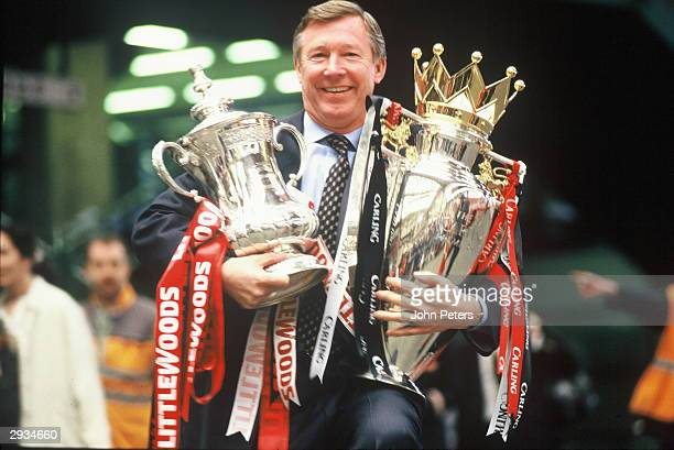 Manager Sir Alex Ferguson of Manchester United with the FA Cup and Premiership Trophy at Victoria Station Manchester on May 12 1996 after completing...
