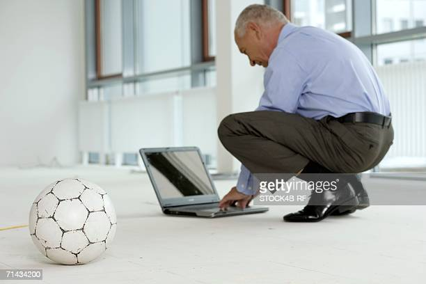 Manager squatting on the floor in front of a laptop, a soccer ball in the foreground