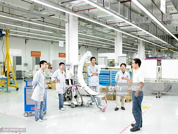 Manager talking to team in medical manufacture plant