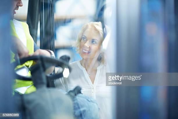 Manager sprechen mit Gabelstapler operator im warehouse