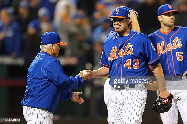 Manager Terry Collins talks with Addison Reed of the New York Mets as he walks off the mound after being relieved in the twelfth inning against the...