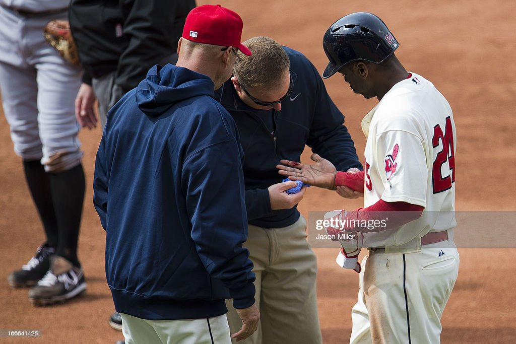Manager <a gi-track='captionPersonalityLinkClicked' href=/galleries/search?phrase=Terry+Francona&family=editorial&specificpeople=171936 ng-click='$event.stopPropagation()'>Terry Francona</a> #17 and assistant trainer Jeff Desjardins look at the hand of <a gi-track='captionPersonalityLinkClicked' href=/galleries/search?phrase=Michael+Bourn&family=editorial&specificpeople=835742 ng-click='$event.stopPropagation()'>Michael Bourn</a> #24 of the Cleveland Indians after Bourn was stepped on during a play at first base during the eighth inning at Progressive Field on April 14, 2013 in Cleveland, Ohio. The White Sox defeated the Indians 3-1.