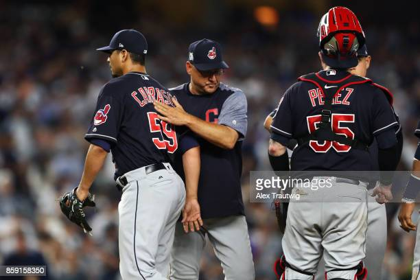 Manager Terry Francona pats pitcher Carlos Carrasco of the Cleveland Indians on the back as he leaves Game 3 of the American League Division Series...