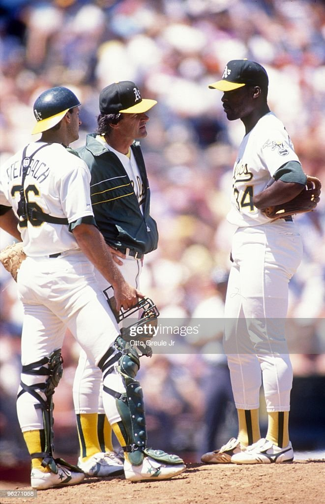 Manager Tony LaRussa of the Oakland Athletics speaks with pitcher Dave Stewart as catcher Terry Steinbach looks on during nn MLB game circa 1988 at...
