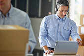 Manager Using Headset In Distribution Warehouse Working On Laptop