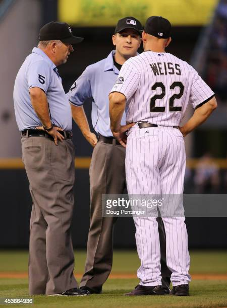 Manager Walt Weiss of the Colorado Rockies talks with umpires Dale Scott and Ben May following a force out play against the Cincinnati Reds at second...