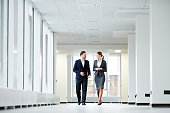 Confident business colleagues walking down in office building and talking