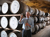Manager with whisky sample next to ageing whisky barrels in distillery