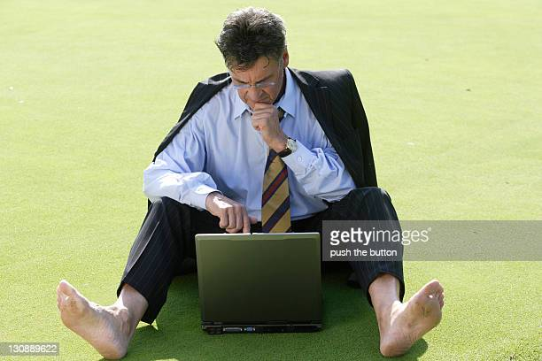 Manager working with notebook barefoot on green