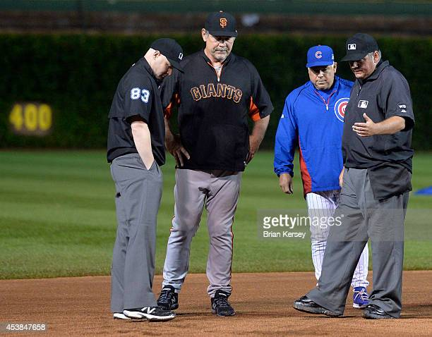 Managers Bruce Bochy of the San Francisco Giants and Rick Renteria of the Chicago Cubs discuss the condition of the field with the umpires Will...
