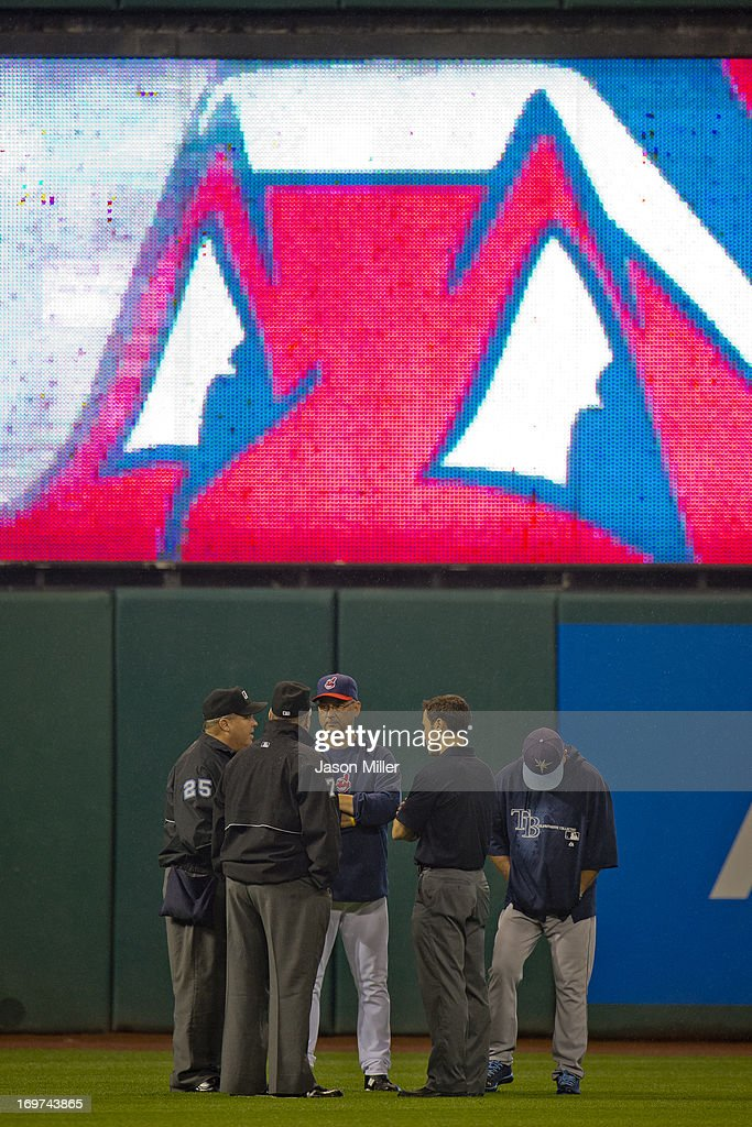 Managers <a gi-track='captionPersonalityLinkClicked' href=/galleries/search?phrase=Joe+Maddon&family=editorial&specificpeople=568433 ng-click='$event.stopPropagation()'>Joe Maddon</a> #70 of the Tampa Bay Rays and <a gi-track='captionPersonalityLinkClicked' href=/galleries/search?phrase=Terry+Francona&family=editorial&specificpeople=171936 ng-click='$event.stopPropagation()'>Terry Francona</a> #17 of the Cleveland Indians discus the weather with umpires Fieldin Culbreth #25 and <a gi-track='captionPersonalityLinkClicked' href=/galleries/search?phrase=Brian+O%27Nora&family=editorial&specificpeople=545809 ng-click='$event.stopPropagation()'>Brian O'Nora</a> #7during a rain delay at Progressive Field on May 31, 2013 in Cleveland, Ohio.