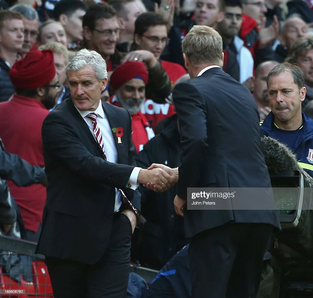 Managers Mark Hughes of Stoke City (L) and David Moyes of Manchester United shake hands after the Barclays Premier League match between Manchester United and Stoke City at Old Trafford on October 26, 2013 in Manchester, England.
