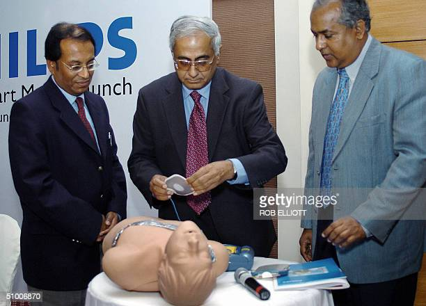 Managing Director and CEO Philips India Limited K Ramachandran applies patches to a dummy's chest during a demonstration at the launch of HeartStart...