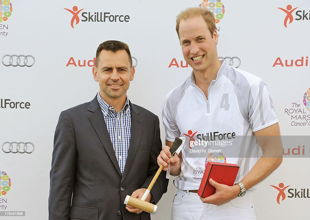 Managing Director of Audi UK Martin Sander (L) presents Prince William, Duke of Cambridge, with a baby polo mallet during day 1 of the Audi Polo Challenge at Coworth Park Polo Club on August 3, 2013 in Ascot, England.