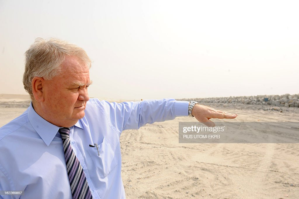 Managing Director of South Energyx Nigeria limited David Frame gestures, on January 31, 2013 in Lagos, at the building site of the three and a half kilometre long sea defence barrier called 'The Great Wall of Lagos' built to shield from coastal erosion Eko Atlantic, a new city born from the Altantic ocean in Lagos. Nigeria's President Goodluck Jonathan and former US President Bill Clinton dedicated on February 21, 2013 the new 5-million-square-metre Eko Atlantic City, which is to be the first modern smart city in Africa to be built on reclaimed land from the Atlantic Ocean. AFP PHOTO/PIUS UTOMI EKPEI