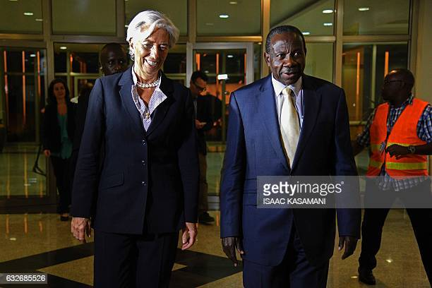 Managing Director of the International Monetary Fund Christine Lagarde walks next to Ugandas Minister of Finance Planning and Economic Development...