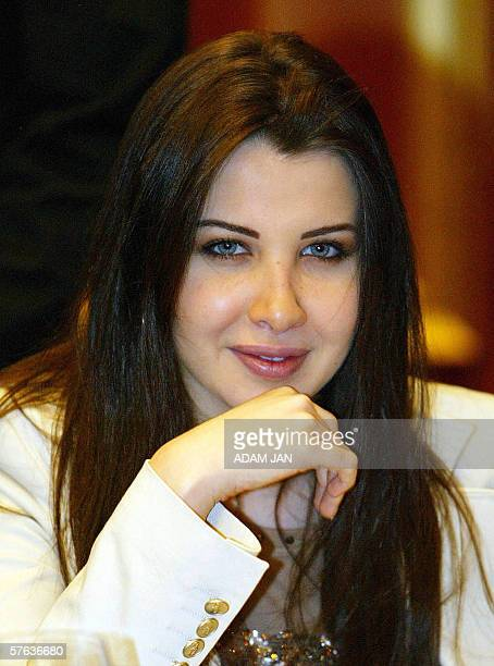 Lebanese Arab pop singer Nancy Ajram holds a bouquet of flowers upon her arrival to Manama 17 May 2006 Ajram is planning to host a live concert 19...