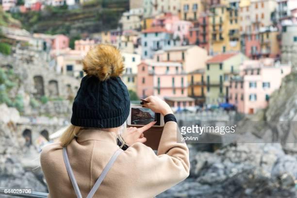 Manarola - woman capturing photo on phone