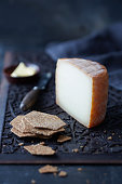Manchego cheese with crackers and butter on a dark carved wooden surface with cheese knife