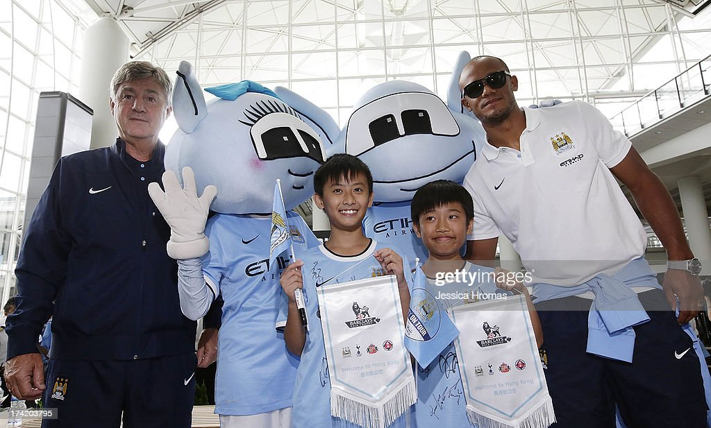 Manchester City Assistant coach Brain Kidd (L) posses for a photo with the Manchester City mascots, Hong Kong fans Edison Lai (12 year old), Andrew Lo (11year old) and team captain Vincent Kompany (R) at Hong Kong Airport after the team arrives to compete in the Barclays Asia Trophy, on July 22, 2013 in Hong Kong.